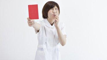 Frau in Pflegeuniform zeigt rote Karte und bläst in eine Trillerpfeife